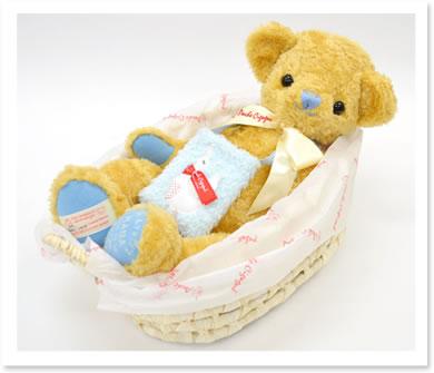 20thアニバーサリーゴールドのベア赤ちゃんを運ぶ「クーファン」に使われる自然素材「メイズ」のバスケットに寝かせてお届けします。