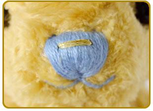 テディベアの文鼻の刺繍は、ゴールドは深い水色、オフホワイトは薄い水色。